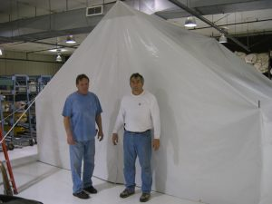 Haiti disaster relief tent, exterior. Two of our team members stand outside of tent to show that size provides enough space to stand.