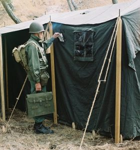 CW4 Bundgaard demonstrating message flap, Command Post Tent, World War II (WWII)